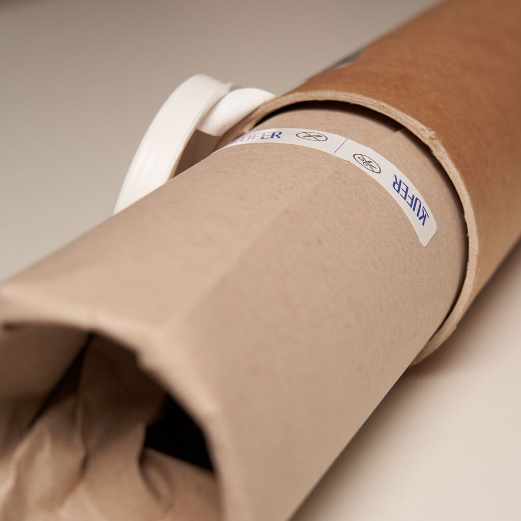 photo - a tube with a poster wrapped in paper with stickers from kufer.pl